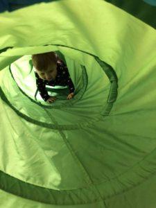 An infant crawls through a fabric tunnel