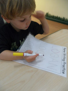 A three year old child practices writing his name.